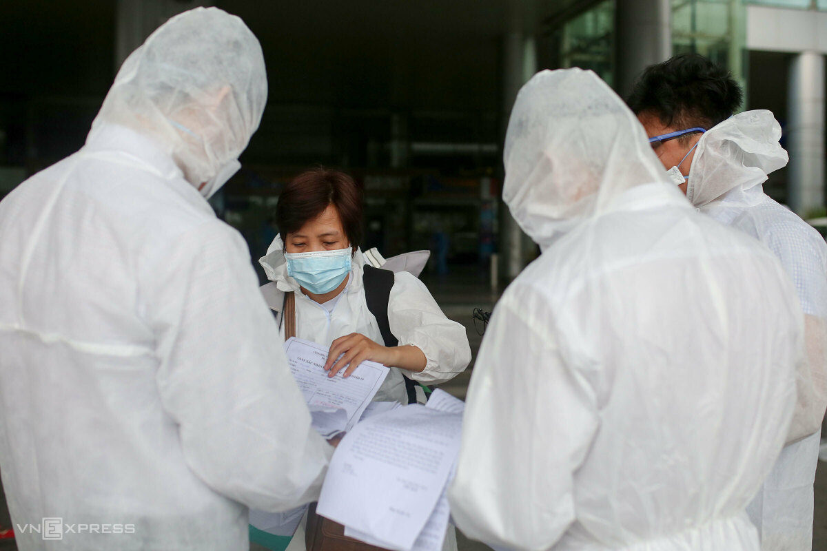 A returnee showed her documents before receiving quarantine instruction from the local authorities.  Those who have been fully vaccinated and have a tested negative result within seven days are allowed to self-isolate in seven days, those receiving one dose must be quarantined in hotels for 14 days and pay the fee.