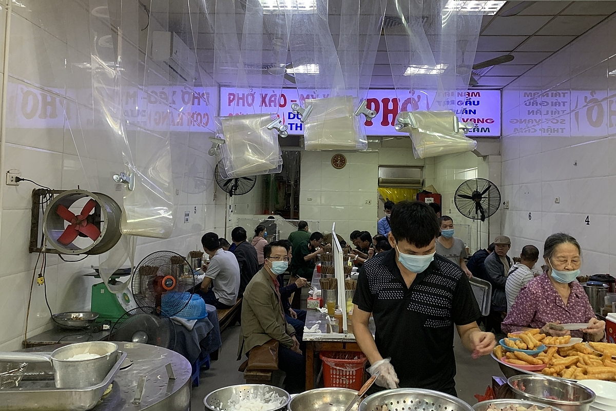 From 6:00 a.m. on October 14, Hanoi permits restaurants and food service enterprises (save for alcoholic beverages, beer, and draft beer businesses) to do business and serve on the spot, with a limit of 50 percent of seats and the use of partitions or barriers. Customers must scan the QR code when the facility owner and employees have been immunized with two doses of the Covid-19 vaccine. Many businesses, especially pho restaurants, were busy serving clients immediately after the order was lifted.