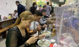 Foodies storm pho shops as Hanoi resumes indoor dining