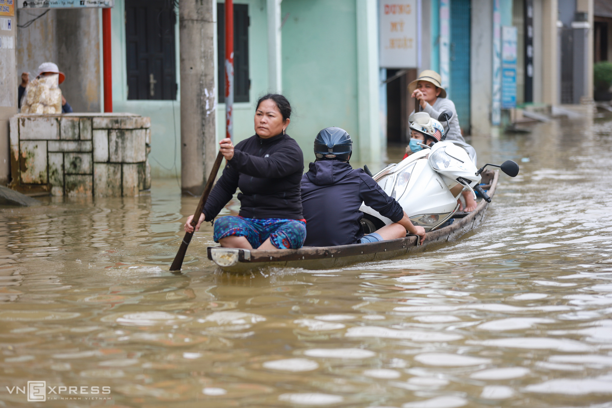 People use an aluminum boat to travel through a flooded street in Bao Vinh town in Thua Thien-Hue Province, central Vietnam, November 2020. Photo by VnExpress/Vo Thanh