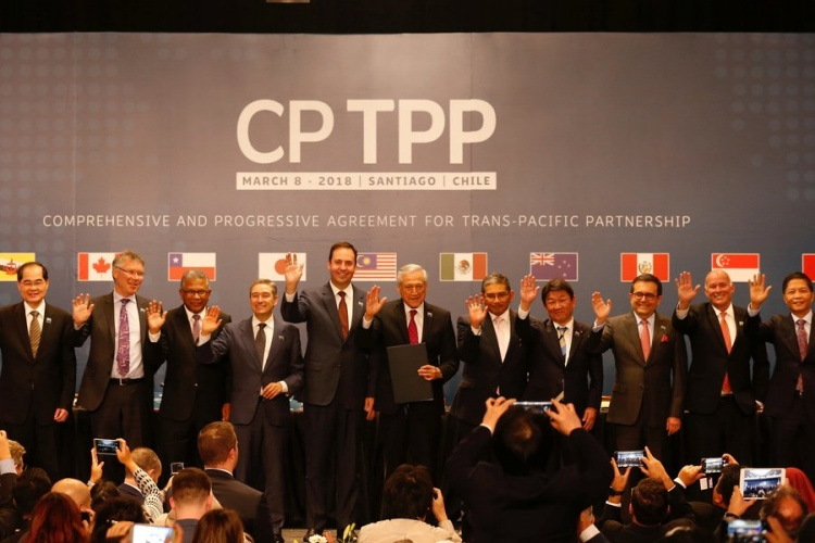 Representatives of members of Trans-Pacific Partnership (TPP) trade deal wave as they pose for an official picture after the signing agreement ceremony in Santiago, Chile March 8, 2018. Photo by Reuters.